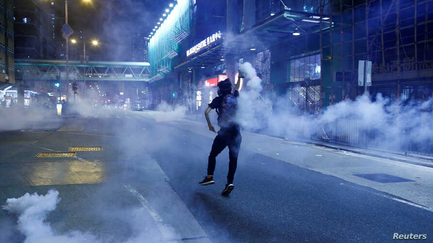 An anti-extradition bill protester throws a tear gas cartridge during clashes with police in Sham Shui Po in Hong Kong, China August 14, 2019.  REUTERS/Thomas Peter