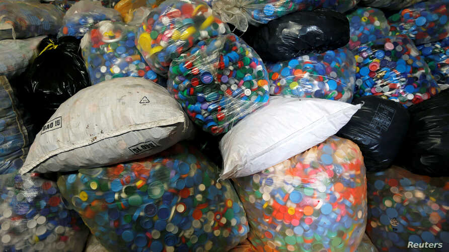 FILE PHOTO: Bags filled with caps are pictured at the Association Bouchon d'Amour, which collects and recycles plastic caps in Martignas-Sur-Jalles, near Bordeaux, France, November 23, 2018. REUTERS/Regis Duvignau/File Photo