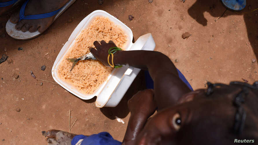 A displaced child, who fled with others from his village in northern Burkina Faso following attacks by assailants, eats inside a school on the outskirts of Ouagadougou, Burkina Faso June 15, 2019. Picture taken June 15 , 2019. REUTERS/Anne Mimault