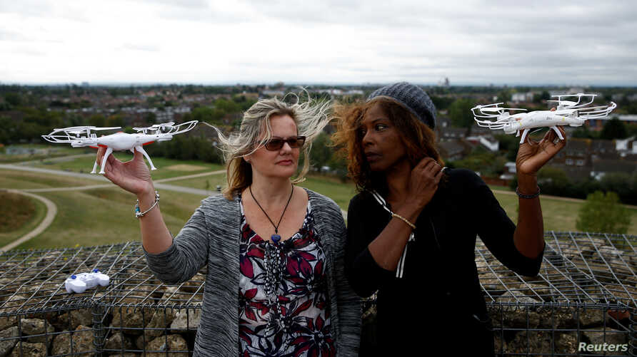 Activists Valerie Milner-Brown and Linda Davidsen pose with drones near Heathrow Airport in London, Britain, September 12, 2019. REUTERS/Henry Nicholls