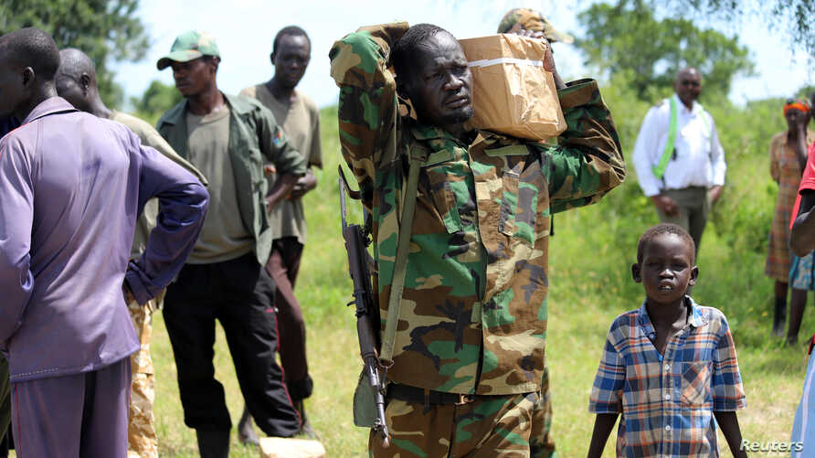 An armed man carries boxes with forms delivered by members of Joint Military Ceasefire Commission (JMCC), meant to select soldiers from the opposition and the government into the South Sudanese military, at the Ayod Barrack in Fangak State, South Sudan, September 13, 2019.REUTERS/Samir Bol
