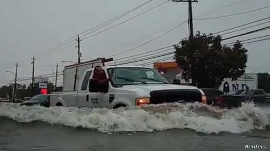 A car passes through a flooded street as storm Imelda hits Houston, Texas, U.S., September 19, 2019 in this screen grab obtained from social media video. @kingjames.daniel/via REUTERS ATTETNION EDITORS - THIS IMAGE HAS BEEN SUPPLIED BY A THIRD PARTY. MANDATORY CREDIT. NO RESALES. NO ARCHIVES