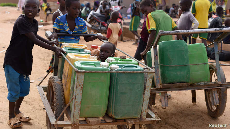 Displaced children that fled from their villages in northern Burkina Faso, following attacks by assailants, push carts loaded…