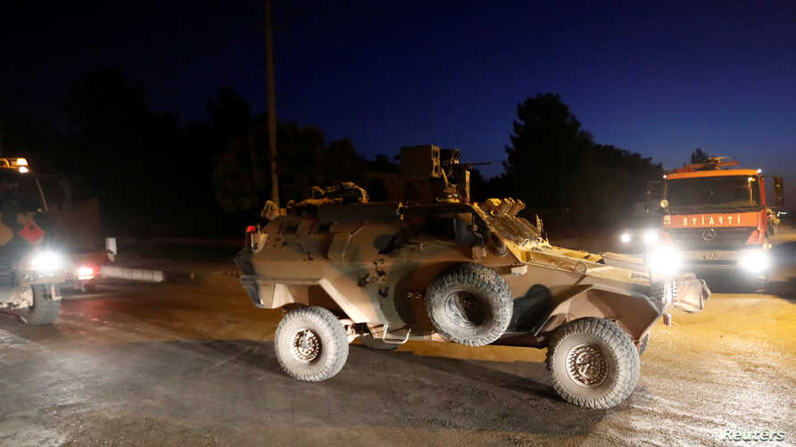 An armored vehicle escorts a Turkish military convoy in the border town of Akcakale in Sanliurfa province, Turkey, October 12,…