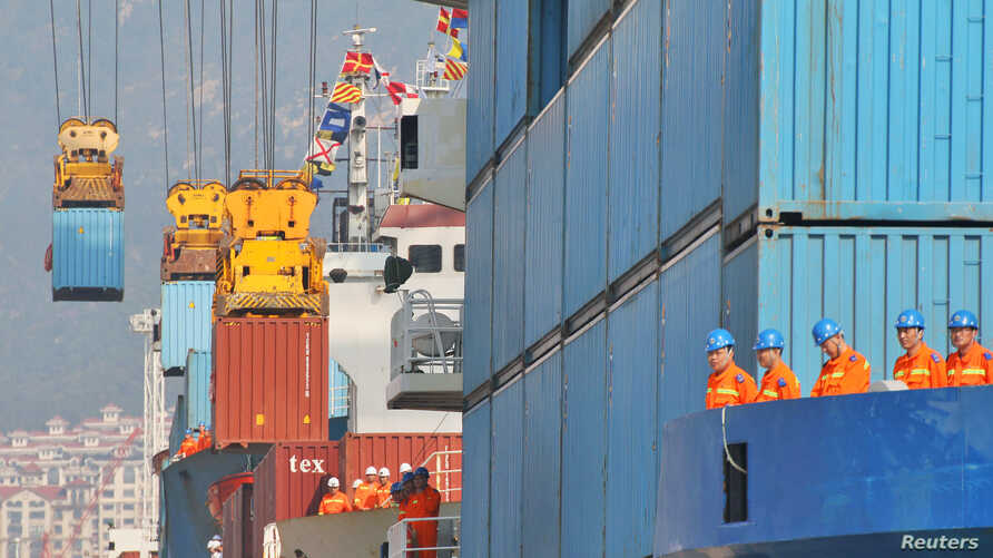 Workers look at cranes lifting containers onto cargo vessels at a port in Yantai, Shandong province, China October 17, 2019…