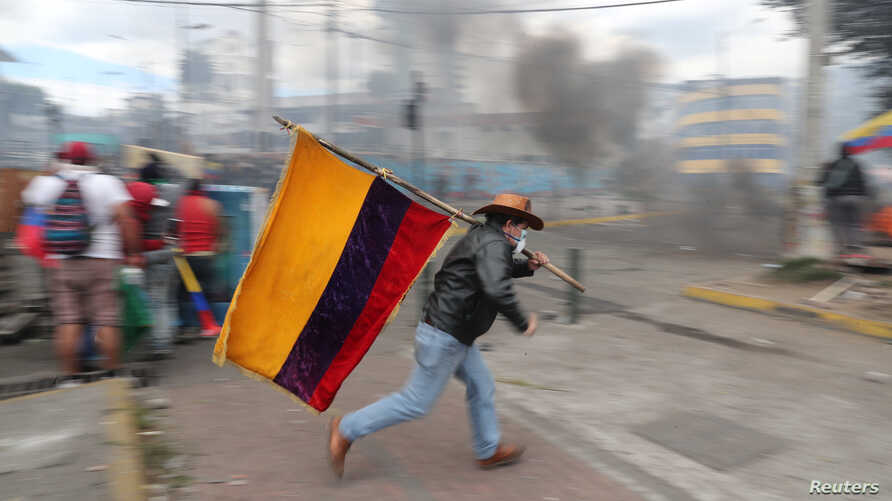 A demonstrator runs while holding an Ecuadorian flag during a protest against Ecuador's President Lenin Moreno's austerity…