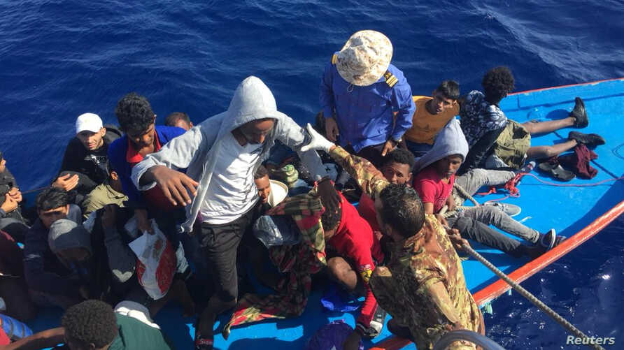 Migrants are seen in a dinghy as they are rescued by Libyan coast guards in the Mediterranean Sea off the coast of Libya,…