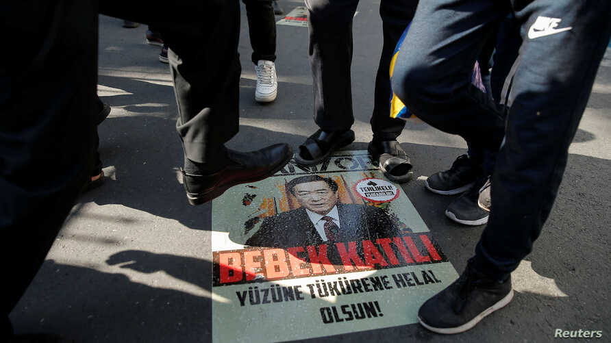 Ethnic Uighur demonstrators step on a poster with an image of Chinese President Xi Jinping during a protest against China in…