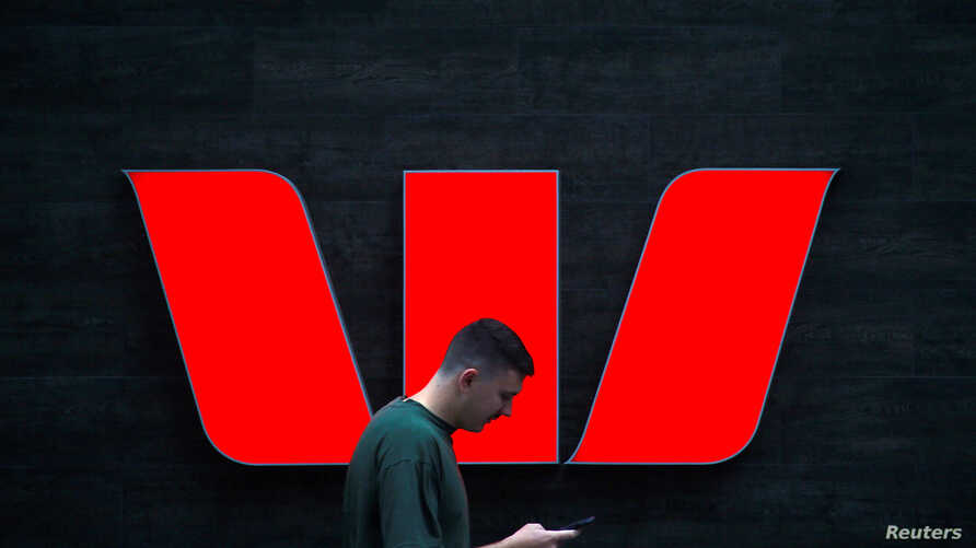 A pedestrian looks at his phone as he walks past a logo for Australia's Westpac Banking Corp located outside a branch in…