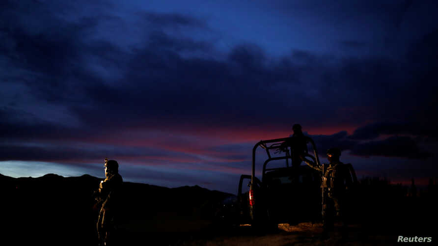 Soldiers assigned to the National Guard keep watch while escorting a caravan of vehicles with relatives and friends arriving…