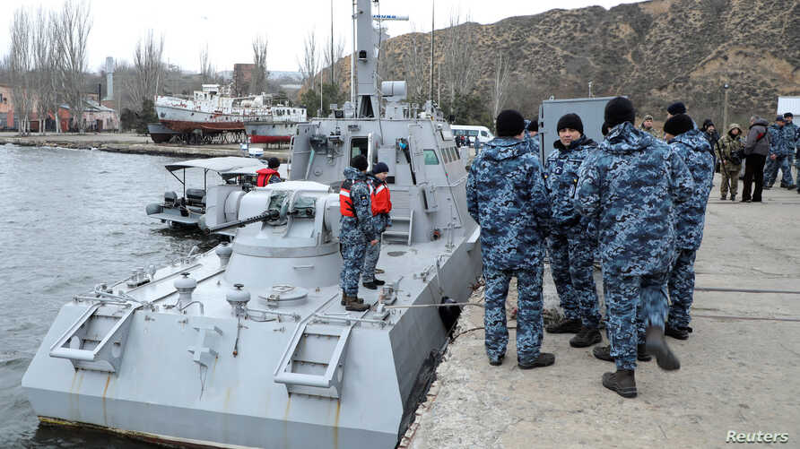 Ukrainian servicemen gather near the vessel Nikopol, one of three Ukraine's naval ships captured in the Kerch Strait and then returned by Russia, in the port of Ochakiv, Nov. 20, 2019.