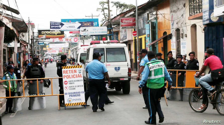 An ambulance passes a police checkpoint to evacuate people from the San Miguel church, where mothers of political prisoners…
