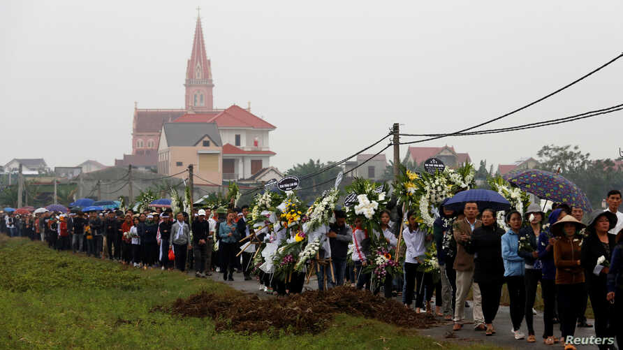 Relatives and villagers of John Hoang Van Tiep and John Nguyen Van Hung, victims who were found dead in the back of a British…