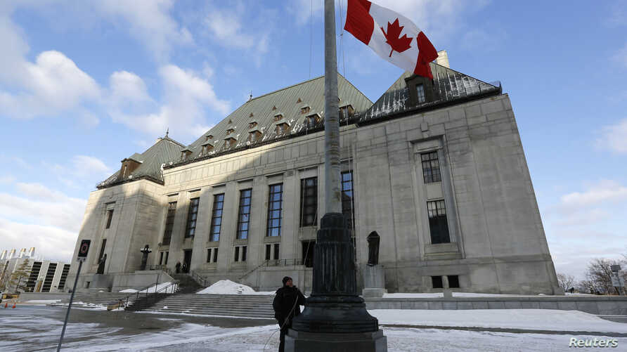 A worker raises a Canadian flag in front of the Supreme Court building in Ottawa March 21, 2014. The Supreme Court of Canada…