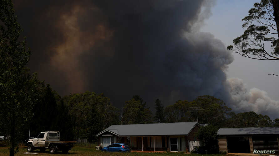 A home is seen as smoke from the Grose Valley Fire rises in the distance, at Bilpin, New South Wales, Australia, December 21,…