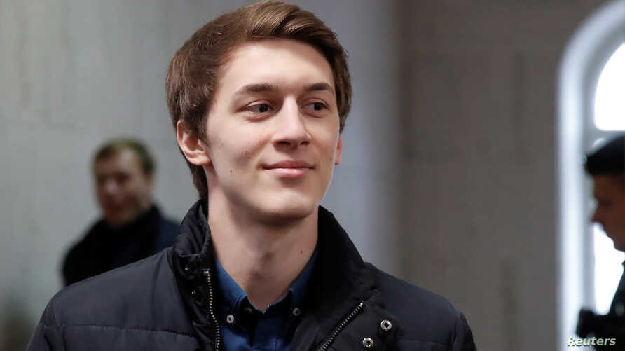Student and blogger Yegor Zhukov, who is under house arrest after being detained at a rally for fair elections, walks inside a…