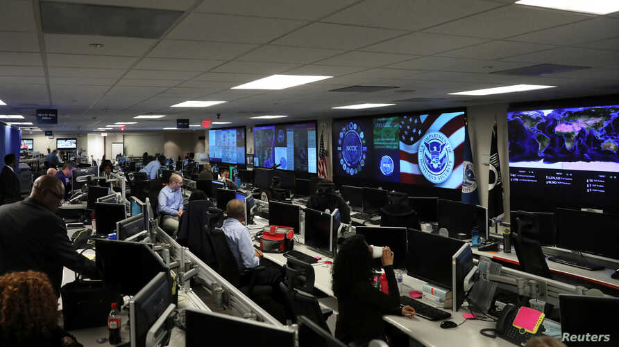 U.S. Department of Homeland Security election security workers monitor screens in the DHS National Cybersecurity and…