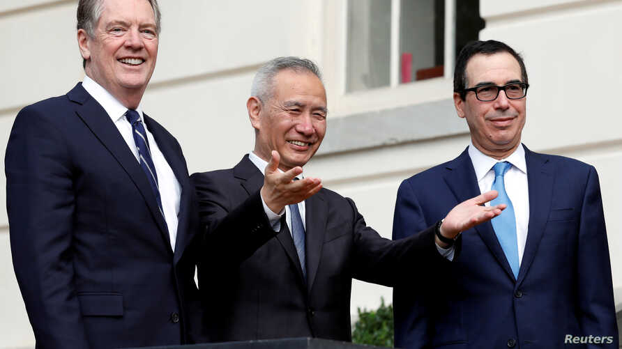 FILE PHOTO: China's Vice Premier Liu He gestures to the media between U.S. Trade Representative Robert Lighthizer (L) and…
