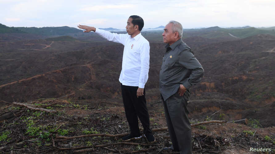 Indonesian President Joko Widodo gestures as Governor of East Kalimantan Isran Noor stands during their visit to an area,…