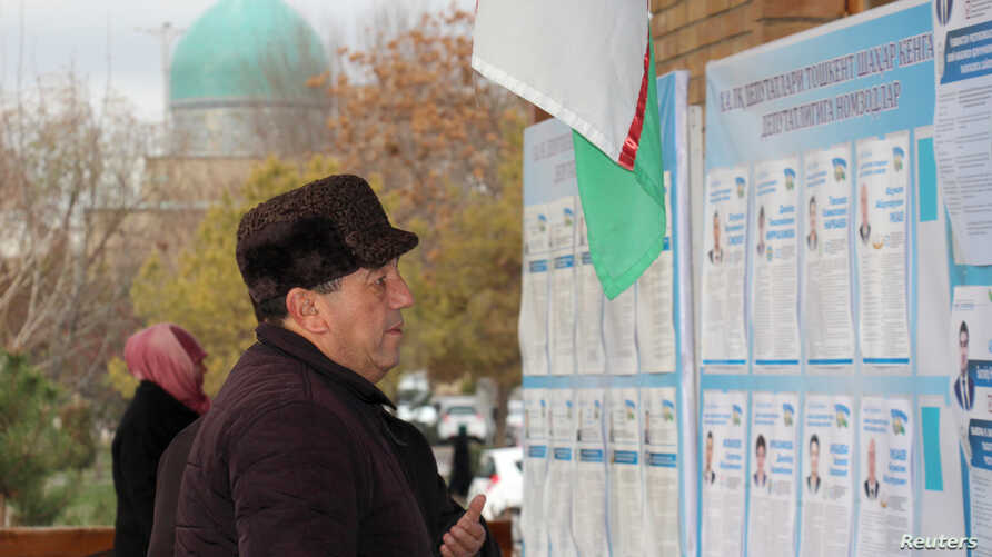 A man reads election candidates posters during parliamentary election in Tashkent, Uzbekistan December 22, 2019.  REUTERS…