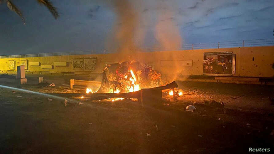 Burning debris are seen on a road near Baghdad International Airport, which according to Iraqi paramilitary groups were caused…