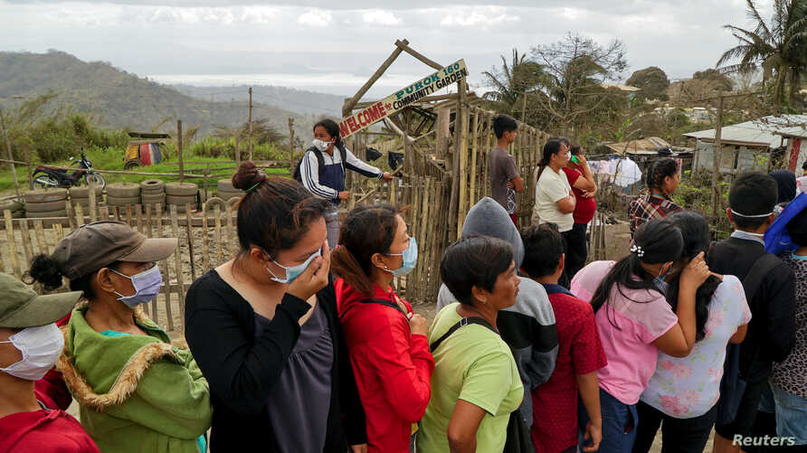Residents, who refuse to evacuate, queue for relief goods following Taal Volcano's eruption, in Talisay, Batangas, Philippines…