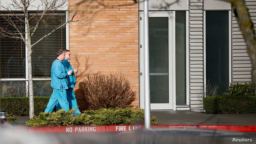 Employees in scrubs walk on the campus at Providence Regional Medical Center after a spokesman from the U.S. Centers for…