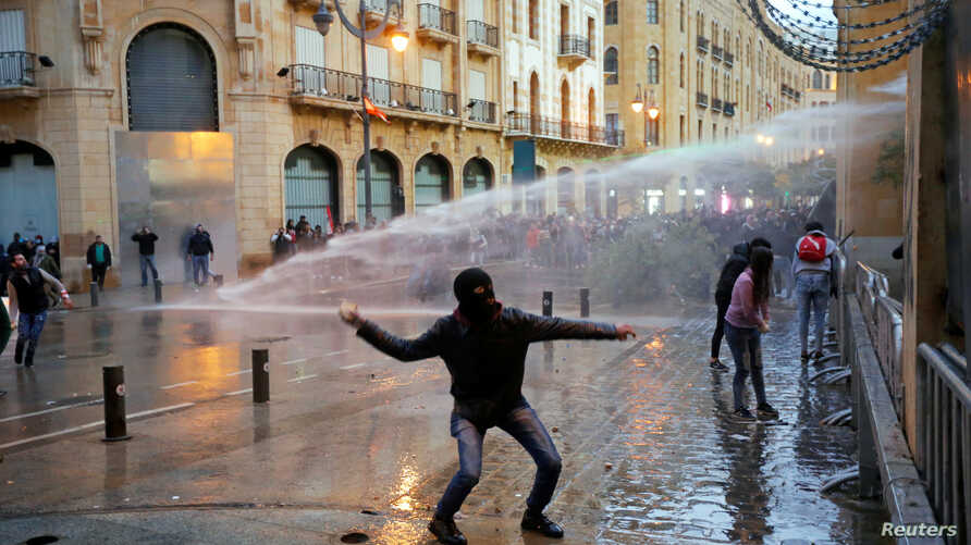 A demonstrator throws a stone as police use water cannon during a protest against the newly formed government in Beirut,…