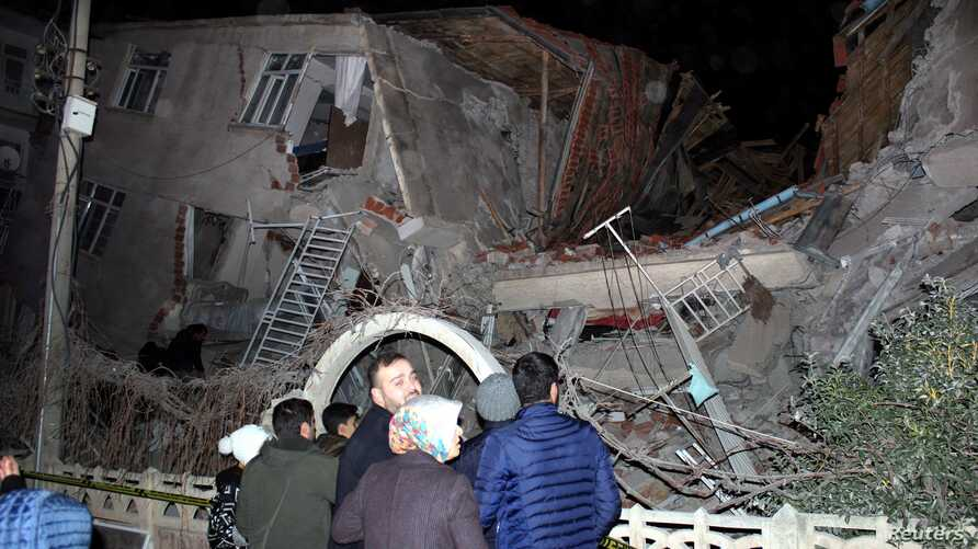 People stand outside a collapsed building after an earthquake in Elazig, Turkey, January 24, 2020. Ihlas News Agency (IHA) via…