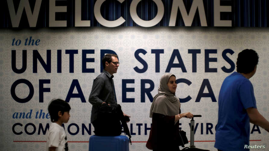 FILE PHOTO: International passengers arrive at Washington Dulles International Airport after the U.S. Supreme Court granted…