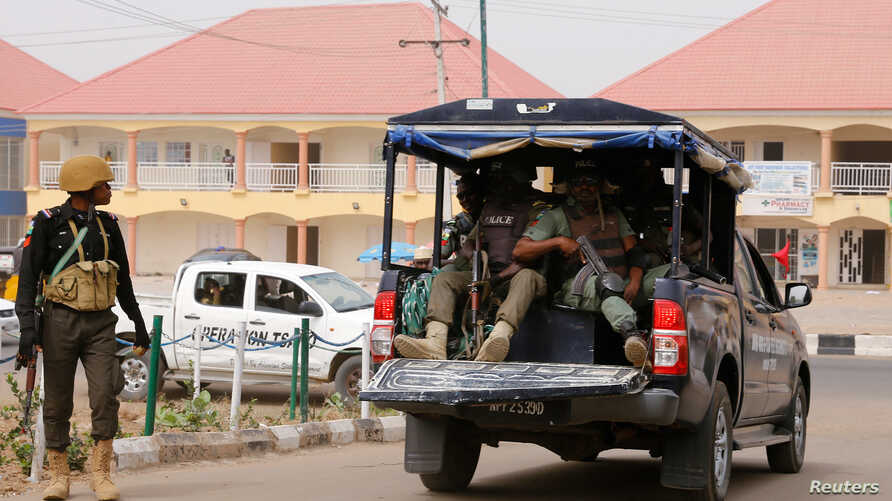 A police vehicle drives out of the INEC office in Yola, in Adamawa State, ahead of the country's presidential election, in Yola…