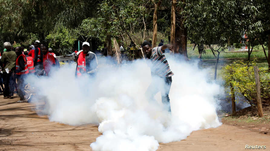 An anti corruption protester kicks a tear gas canisters fired by Kenyan police during a protest in Nairobi, Kenya, April 30,…