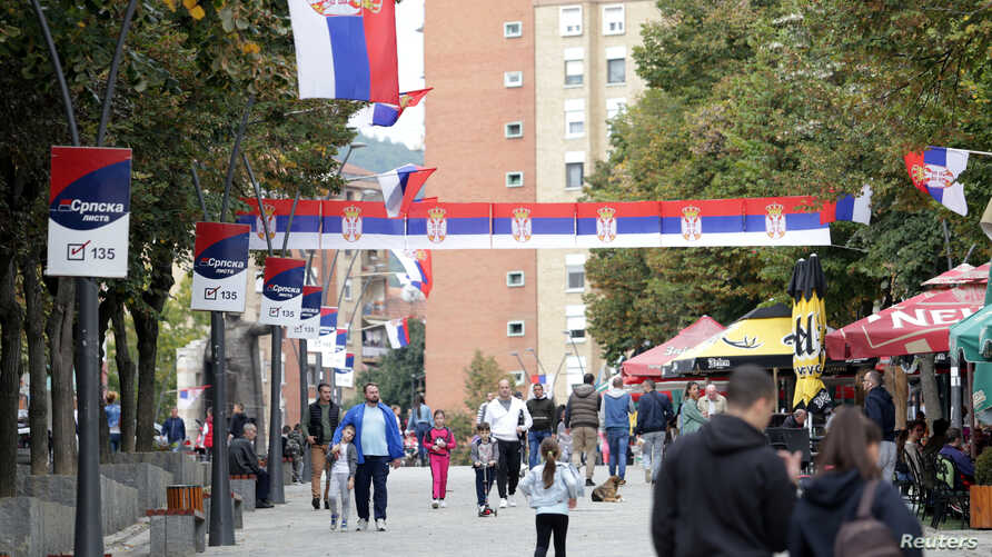 People walk through street decorated with Serbian flags in Mitrovica, Kosovo, October 5, 2019. REUTERS/Florion Goga