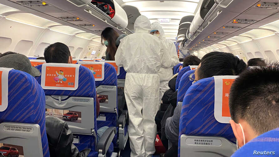 Health workers in protective suits check the condition of a passenger on an airplane that just landed from Changsha, a city in…