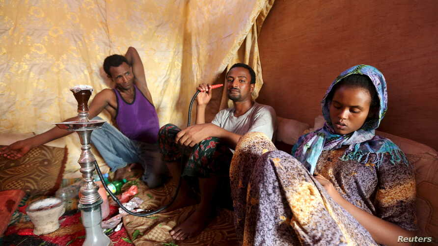Illegal immigrants from Ethiopia attempting to cross into Yemen smoke shisha in their makeshift shelter in Bosasso, northern…