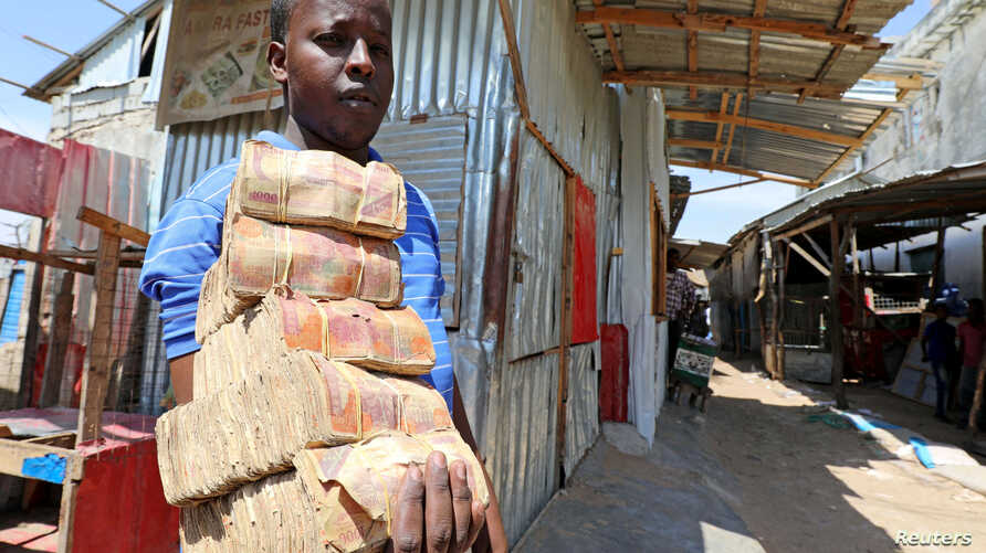 A dealer carries bundles of Somali shilling, the Somalian currency, at an open air currency exchange bureau within the…