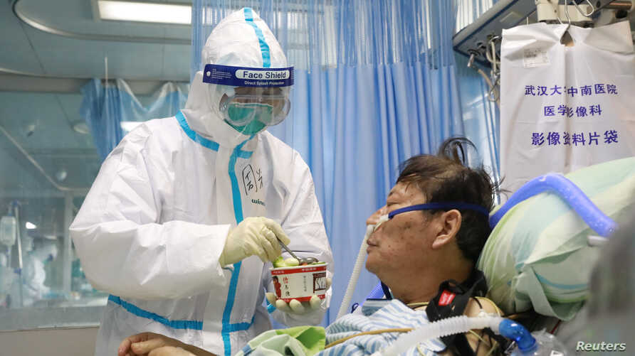 A nurse in a protective suit feeds a novel coronavirus patient inside an isolated ward at Zhongnan Hospital of Wuhan University…