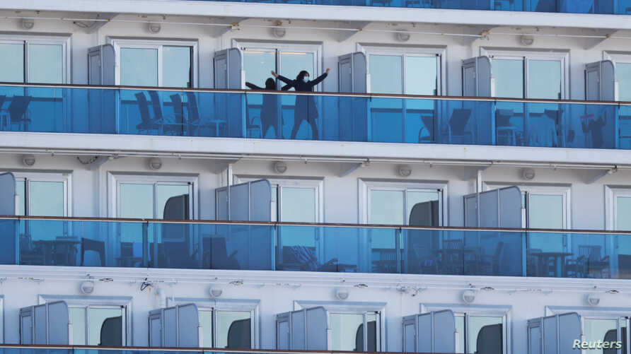 FILE PHOTO: A passenger stretches on the balcony of a cabin of the cruise ship Diamond Princess, where dozens of passengers…
