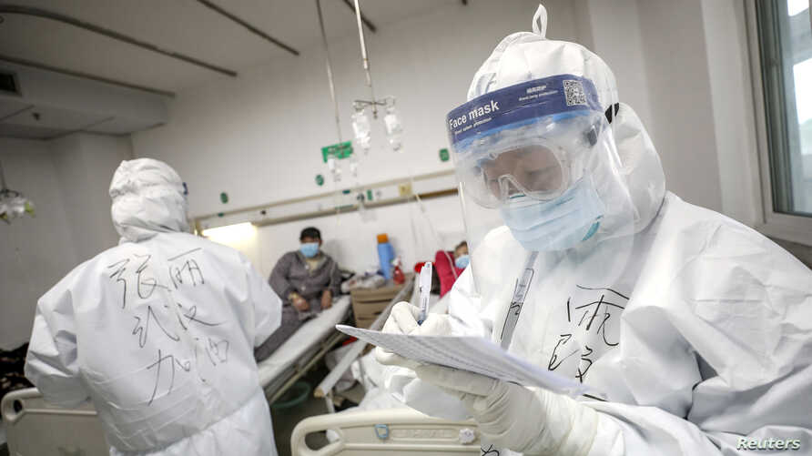 A medical worker in protective suit checks a patient's records at Jinyintan hospital in Wuhan, the epicentre of the novel…