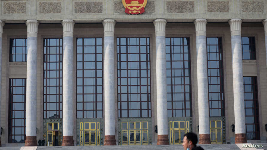 A man with a face mask walks past the Great Hall of the People, as the country is hit by an outbreak of the novel coronavirus,…