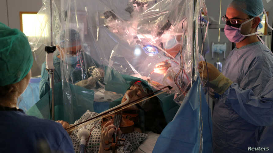 A patient Dagmar Turner, 53, plays violin while surgeons remove her brain tumour at King's College Hospital in London, Britain,…