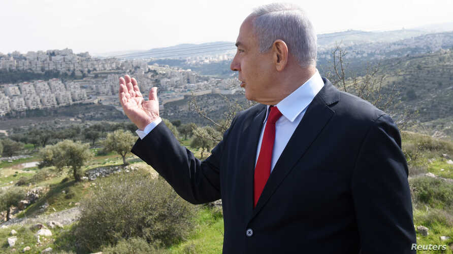 Israeli Prime Minister Benjamin Netanyahu delivers a statement overlooking the Israeli settlement of Har Homa, located in an…
