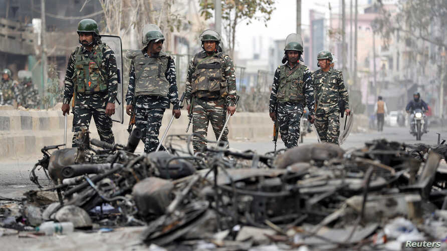 Security forces patrol past charred vehicles in a riot affected area following clashes between people demonstrating for and…