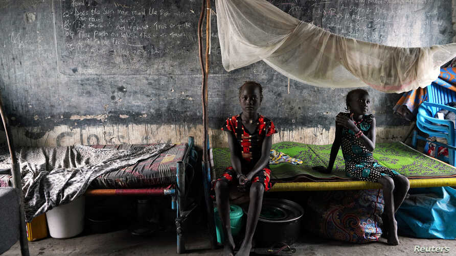 Displaced girls sit on a bed in a classroom, in a school now occupied by IDPs (Internally Displaced People) after heavy rains…