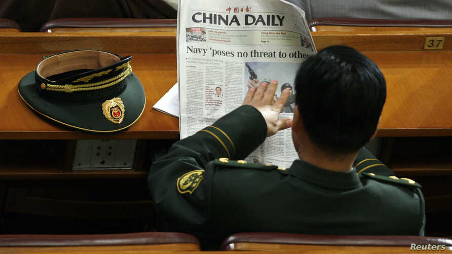 A military delegate reads a China Daily newspaper ahead of the second plenary session of the National People's Congress (NPC)…