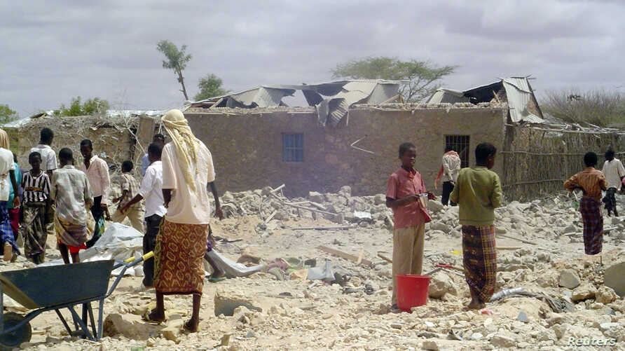 People walk through rubble after U.S. war planes killed an Islamist rebel said to be al Qaeda's leader in Somalia and as many…