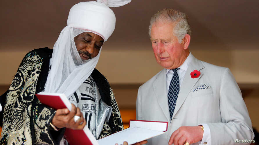 Britain's Prince Charles stands with the Emir of Kano Lamido Sanusi as they look at a book during his meeting with Traditional…