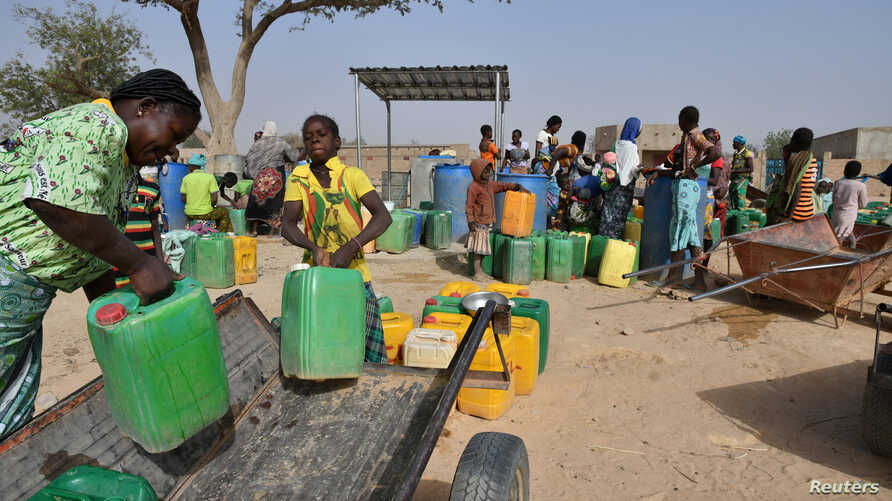 Displaced people, who fled from attacks of armed militants in town of Roffenaga, carry their jerrycans at the water point near…