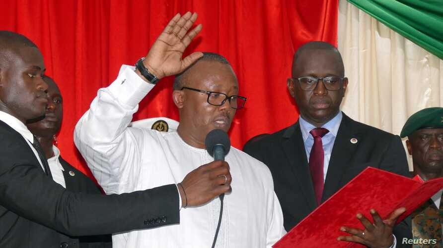 Guinea-Bissau's newly elected president Umaro Cissoko Embalo raises his arm during his swearing-in ceremony in Bissau, Guinea…