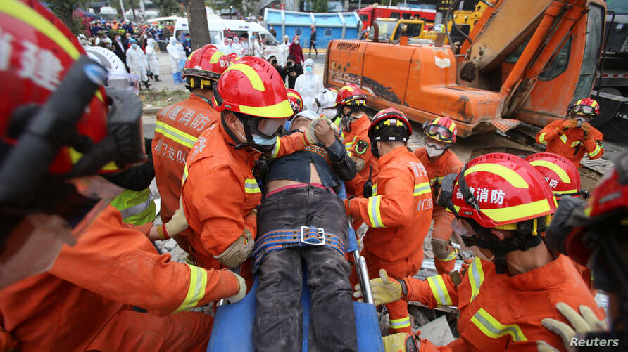 Rescue workers move a casualty at the site where a hotel being used for the coronavirus quarantine collapsed, as the country is…